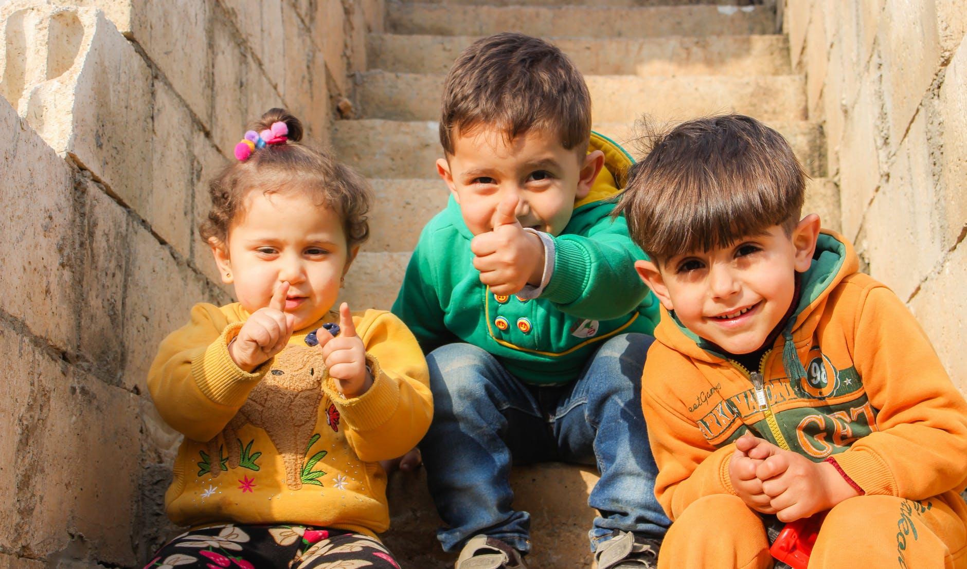 three children sitting on stairs