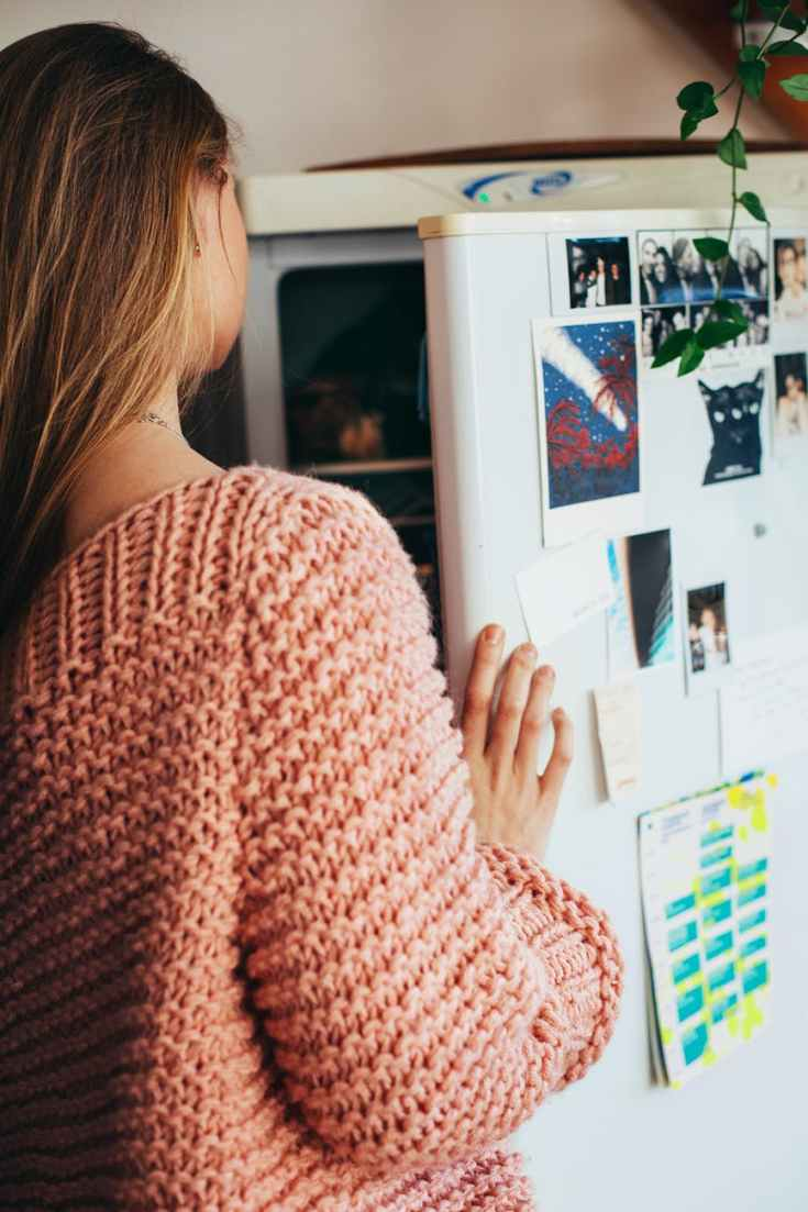 woman wearing pink knit top opening refrigerator