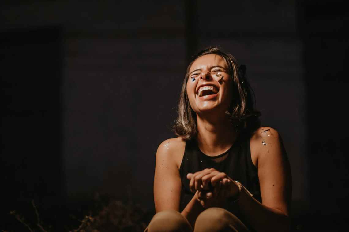 photo of a woman laughing wearing black top